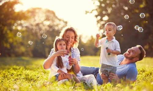 Family-with-children-blow-soap-bubbles-outdoor